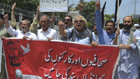 """Pakistani journalists denounce censorship, holding a banner that reads: """"stop sacking journalists,"""" in Peshawar, Pakistan, July 16, 2019."""