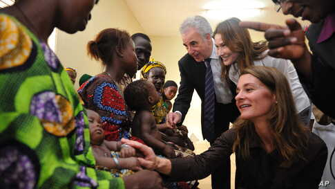 Melinda Gates, seated, visits Benin to speak with long-suffering people during her visit to a hospital in Dangbo in 2010.