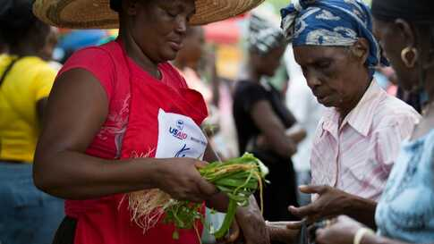 Kore Lavi participant buys food from program vendor. (Photo: USAID)