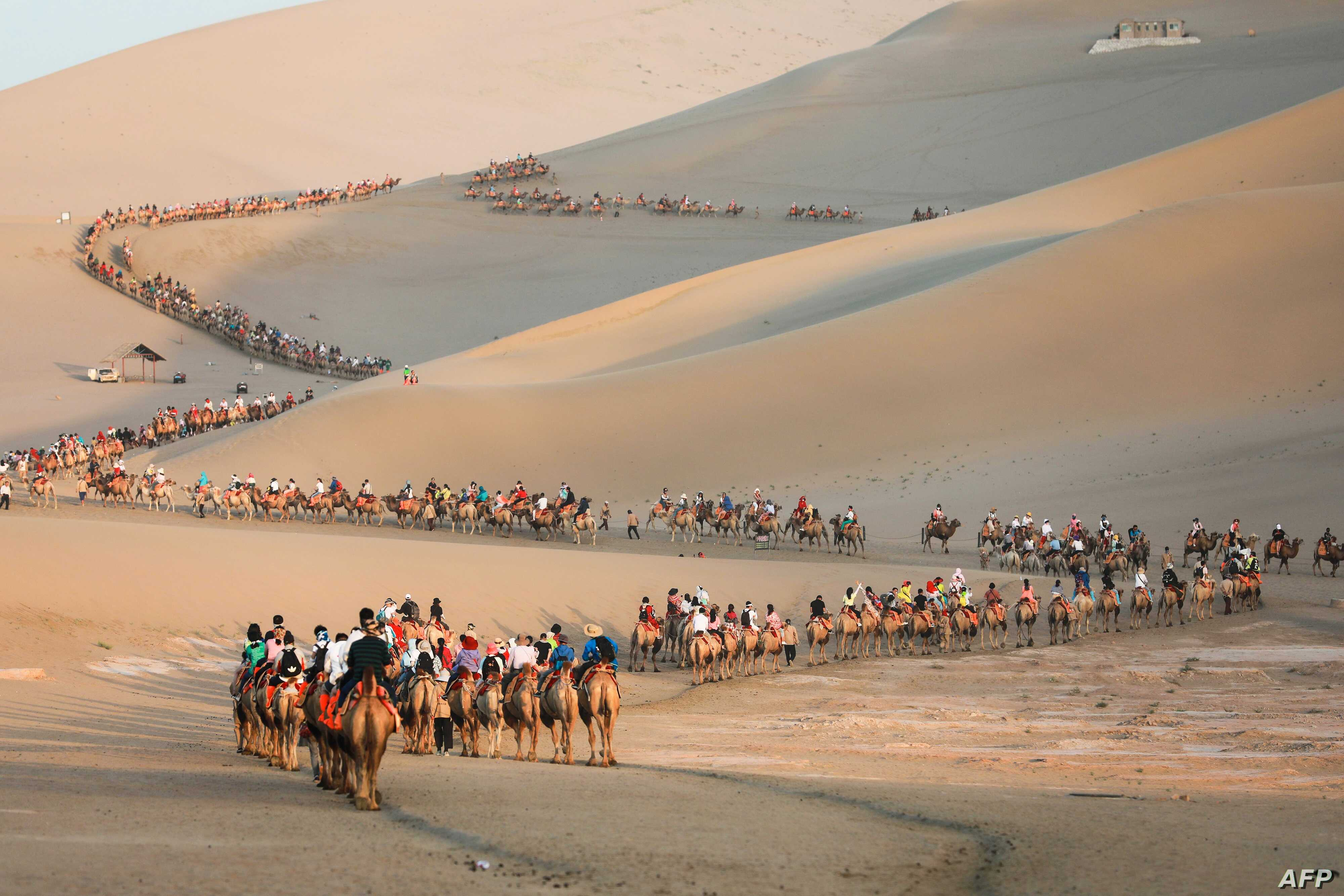 Tourists ride camels in the desert in Dunhuang in China's northwestern Gansu province.