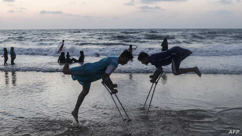 Palestinian amputees Mohammed Eliwa, 17, and Ahmed al-Khoudari (R), 20, who each lost a leg during clashes on the border with Israel, play on the beach in Gaza City, Aug. 20, 2019.