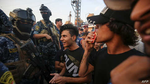 Iraqi protesters speaks with members of police in Baghdad's predominantly Shiite Sadr City, on October 7, 2019. -…