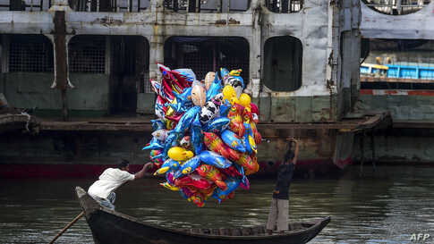 A man holds balloons as he crosses the Buriganga River on a boat in Dhaka, Bangladesh, Oct. 18, 2019.