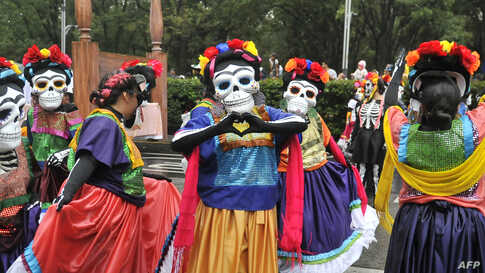 People take part in the Day of the Dead parade along Reforma avenue in Mexico City, Oct. 27, 2019.