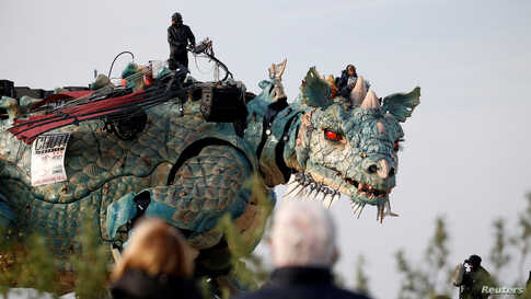 "People look at the ""Dragon de Calais"" by Francois Delaroziere and La compagnie La Machine during a rehearsal in the harbor of Calais, France, Oct. 30, 2019."