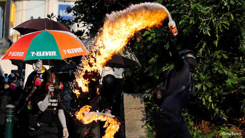 An anti-government demonstrator throws a petrol bomb towards Tsim Sha Tsui Police Station during a protest in Hong Kong, China.