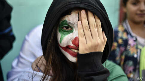An Algerian demonstrator wearing face paint in the colors of the national flag takes part in an anti-government demonstration in the capital Algiers, Nov. 1, 2019.