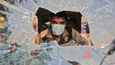A tuktuk (motorized rickshaw) driver sits behind his broken windshield in his vehicle during clashes between anti-government protesters and security forces in the Iraqi capital Baghdad's Rasheed street near al-Ahrar bridge, Nov. 29, 2019.