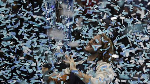 Stefanos Tsitsipas of Greece holds up a trophy and celebrates as confetti falls after defeating Austria's Dominic Thiem in the final of the ATP World Finals tennis match at the O2 arena in London, Nov. 17, 2019.