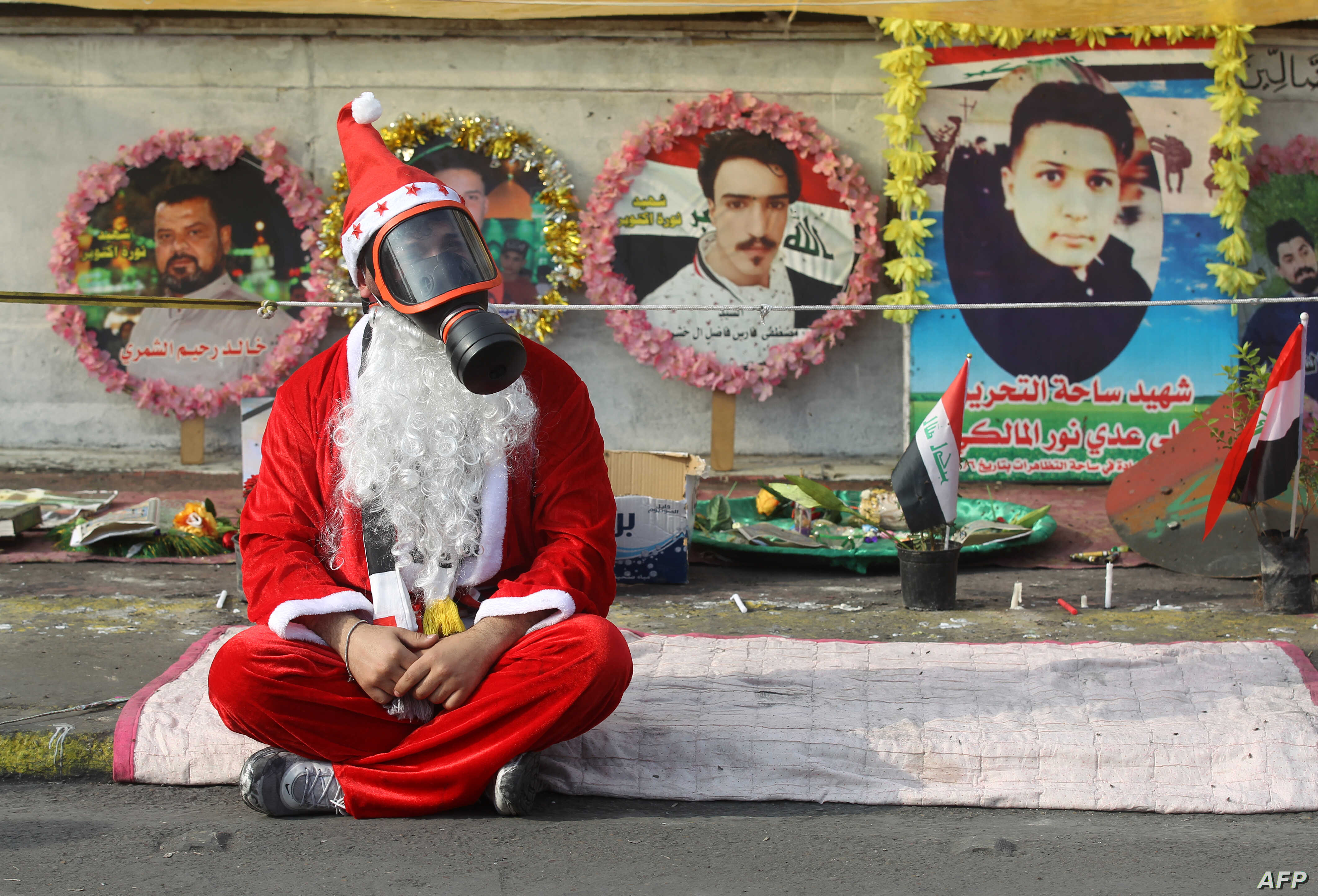 An Iraqi demonstrator wearing a Santa Claus costume and a gas mask sits on a blanket in the capital Baghdad's Tahrir Square, amid ongoing anti-government protests, Dec. 6, 2019.