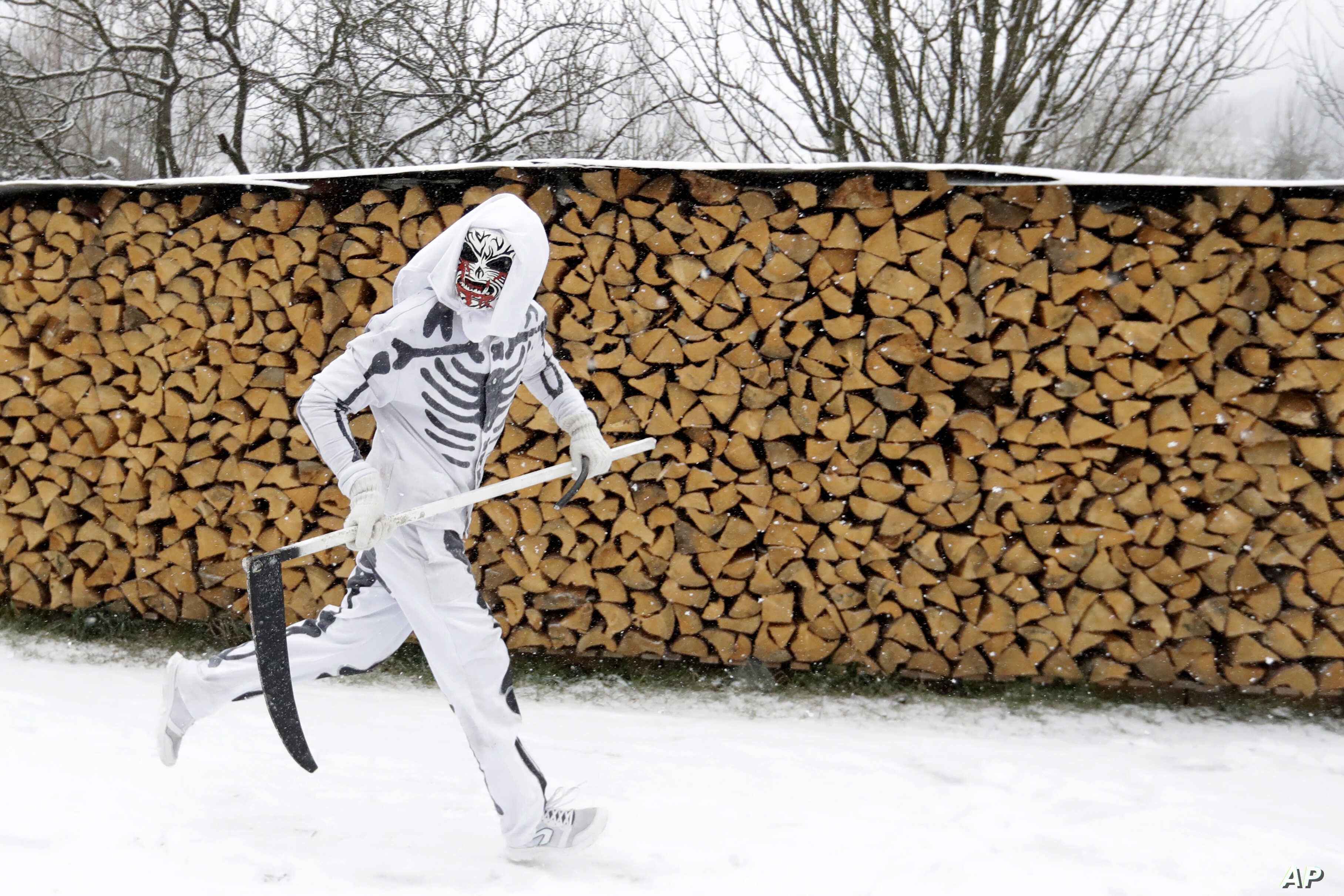 A reveler depicting a grim reaper runs during a traditional St. Nicholas procession in the village of Valasska Polanka, Czech Republic, Dec. 7, 2019.
