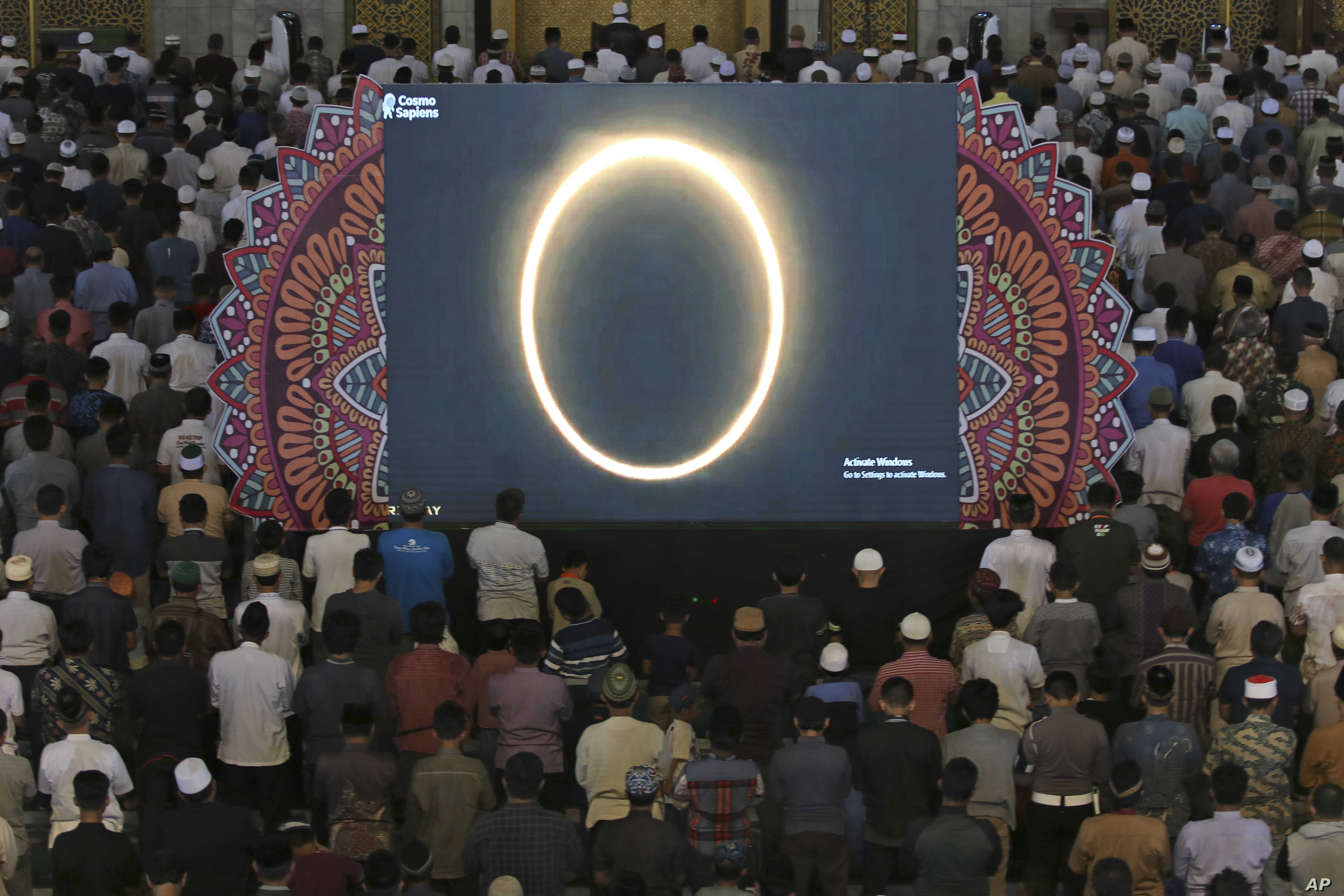 Muslim men perform a special 'kusoof' prayer as a live report of the annular solar eclipse is broadcast on a large screen at a mosque in Surabaya, East Java, Indonesia.