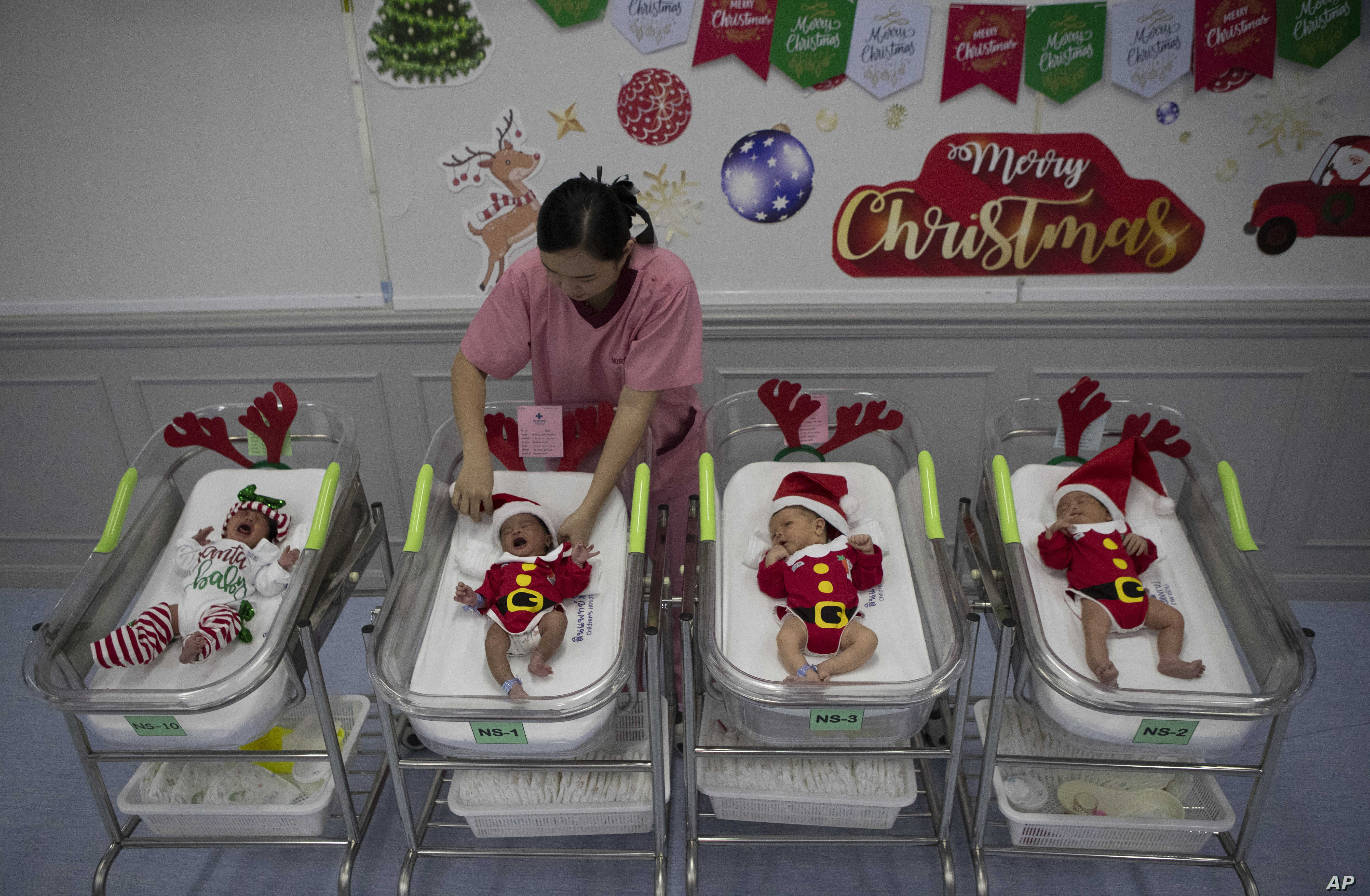 A nurse adjusts the outfits of newborn babies dressed in Santa costumes on Christmas eve at the Synphaet hospital in Bangkok, Thailand, Dec. 24, 2019.