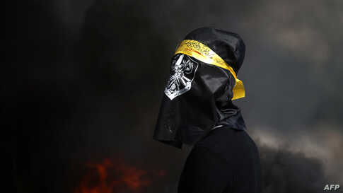 A Palestinian, his face covered by a flag, stands in front of burning tires during clashes with Israeli in the Israeli-occupied West Bank, Jan. 3, 2020.