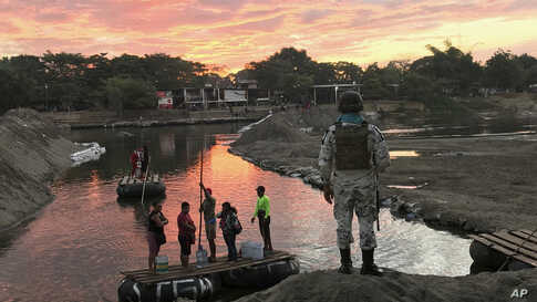 A Mexican National Guard looks at local residents crossing the Suchiate River, near Ciudad Hidalgo, on the Mexican border.