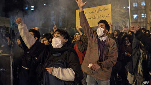 """Protesters chant slogans and hold a placard reading in Farsi """"Your mistake was unintentional, your lie was intentional,"""" during an anti-govenrnment rally outside Amir Kabir University, in Tehran, Iran, Jan. 11, 2020."""