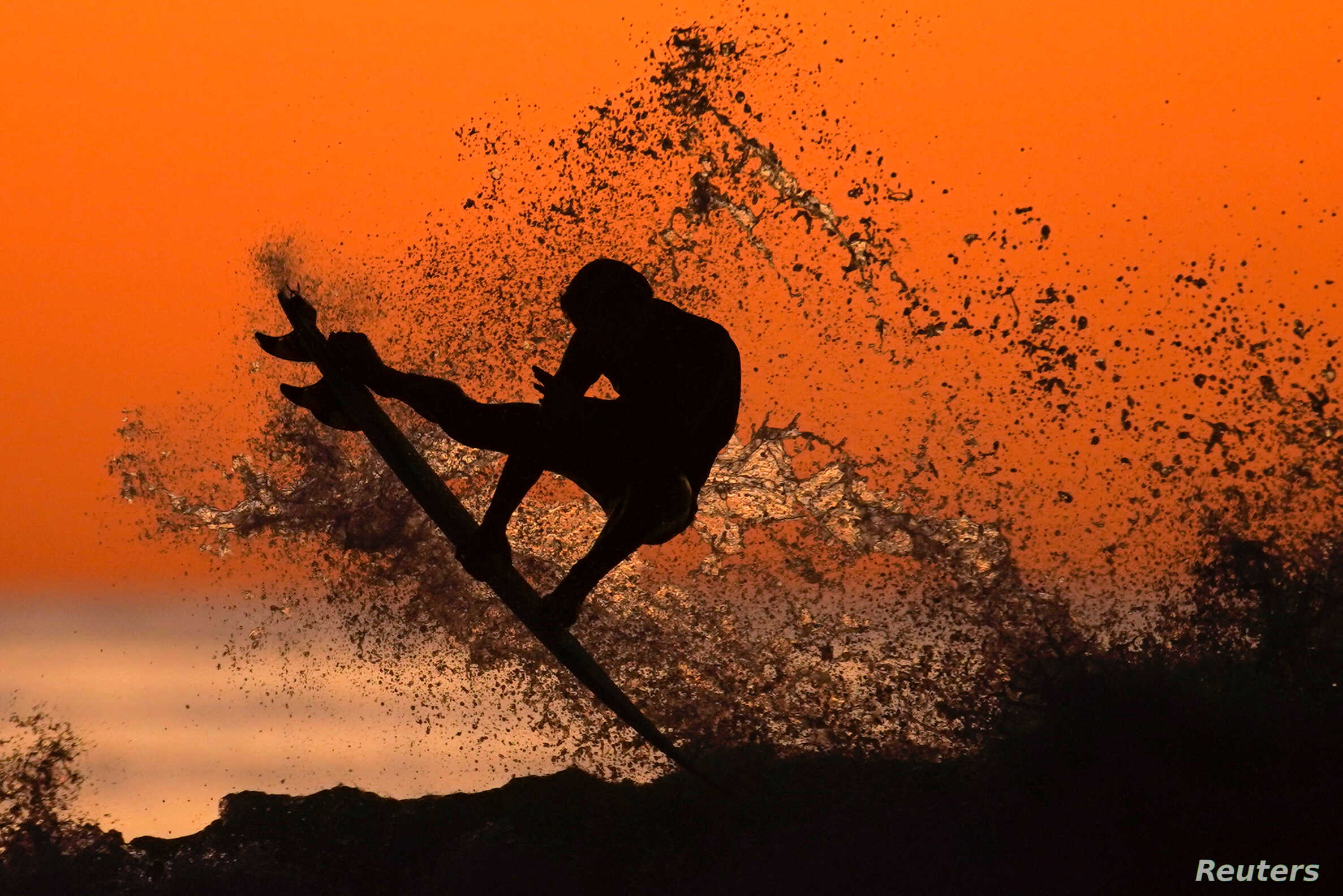 A surfer surfs after sunset in Cardiff, California, Jan. 7, 2020.