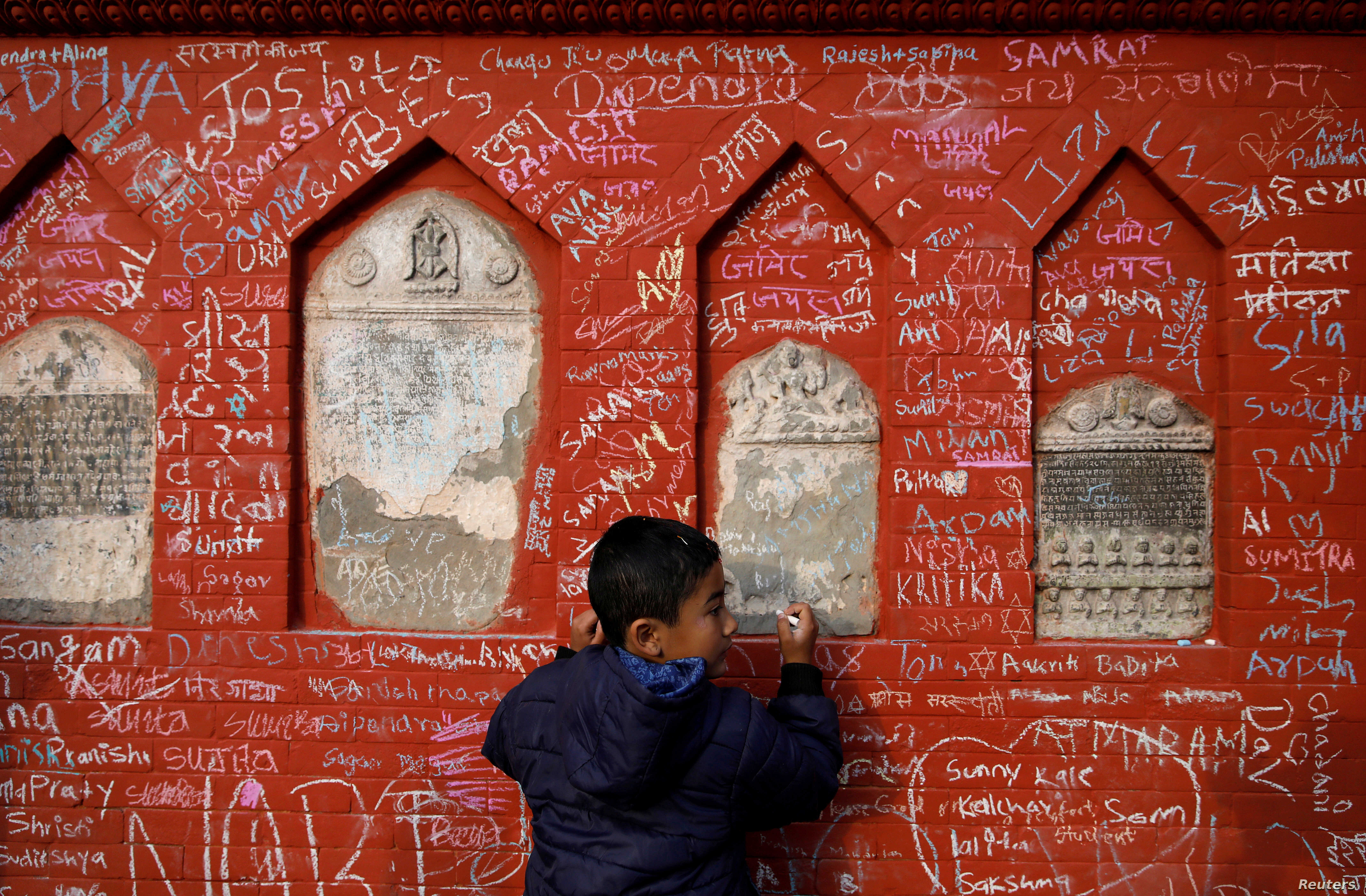 A boy writes on the wall of a Saraswati temple during the Shreepanchami festival dedicated to the goddess of education, Saraswati, in the belief the goddess will help devotees excel in education, in Kathmandu, Nepal.