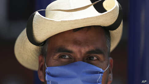 A street vendor wears a mask over his mouth as a precaution against the spread of the new coronavirus in Mexico City, Friday,…