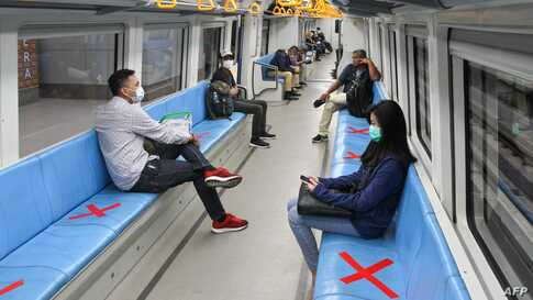 People sit on designated areas decided by red cross marks to ensure social distancing inside a light rapid transit train in…