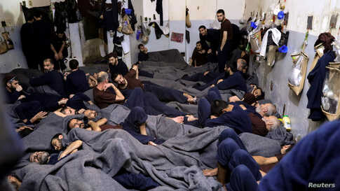 FILE - Foreign prisoners, suspected of being part of the Islamic State, lie in a prison cell in Hasaka, Syria, January 7, 2020.