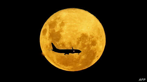 A plane passes in front of the full moon as seen from Curitiba, Brazil, March 9, 2020.