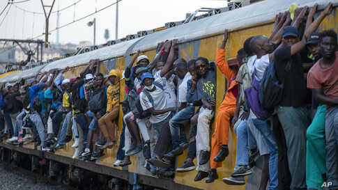 Train commuters hold on to the side of an overcrowded passenger train in Soweto, South Africa.