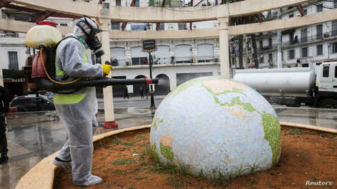 A worker wearing a protective suit disinfects a globe-shaped public garden, following the outbreak of coronavirus disease (COVID-19), in Algiers, Algeria.