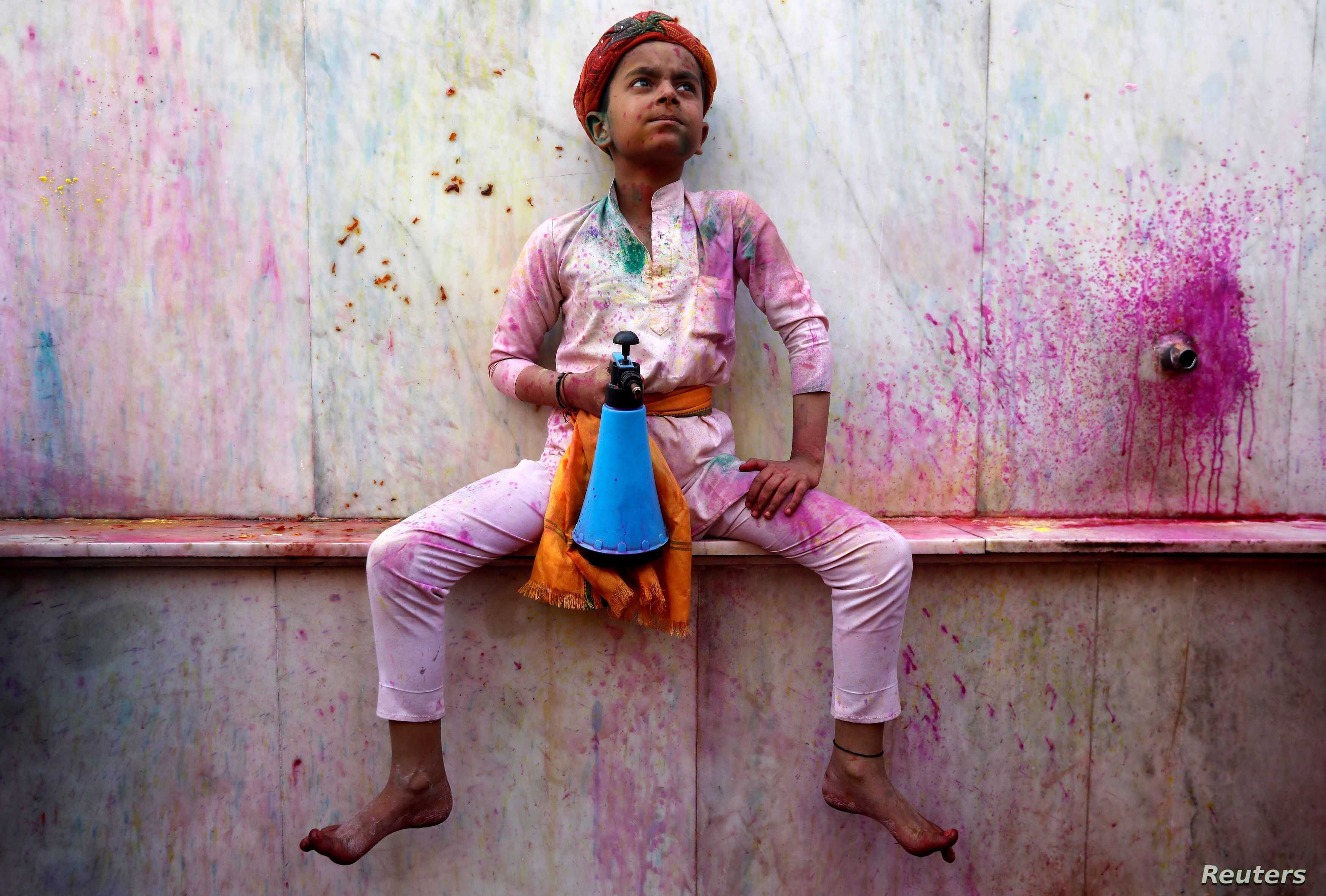A boy holds a spray bottle as he takes part in the religious festival of Holi inside a temple in Nandgaon village, in the state of Uttar Pradesh, India.