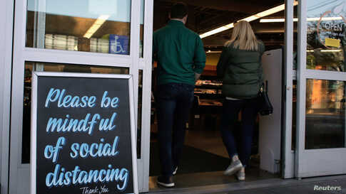 Shoppers enter a grocery store near a sign requesting social distancing, following reports of coronavirus cases in the area in Seattle, Washington, March 17, 2020.