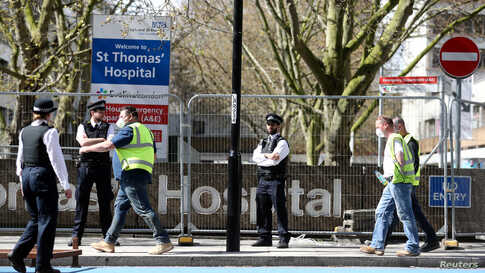 Police officers and building workers are seen outside St Thomas' Hospital in London after British Prime Minister Boris Johnson was admitted with persistent coronavirus (COVID-19) symptoms, London, April 6, 2020.
