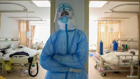 A medical worker in protective suit takes a break at an isolated ward of Wuhan Red Cross Hospital in Wuhan, the epicentre of…