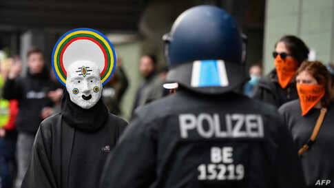 A protestor wearing a mask faces off with Police in Berlin's Kreuzberg district on May 1, 2020, during May Day protests amid…