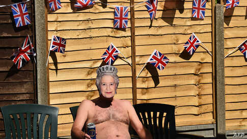 Terry Livesey wearing a mask of Britain's Queen Elizabeth II, sunbathes in his garden surrounded by Union flags as people mark…