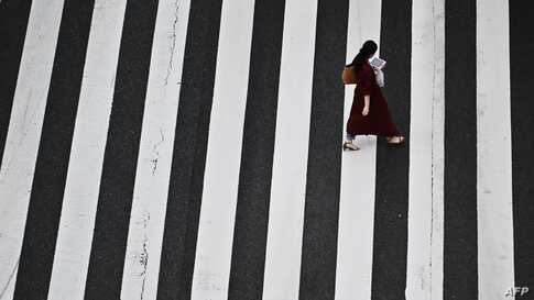 A woman crosses a street in Tokyo's Shinbashi area on May 15, 2020. (Photo by CHARLY TRIBALLEAU / AFP)