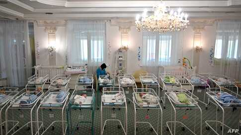 A nurse cares for newborn babies at Kiev's Venice hotel on May 15, 2020. - More than 100 babies born to surrogate mothers have…