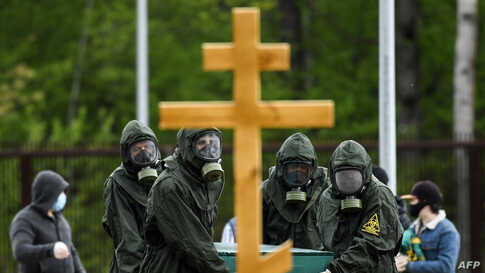 Cemetery workers wearing protective equipment bury a coronavirus victim at a cemetery on the outskirts of Moscow on May 15,…