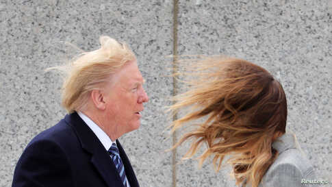 U.S. President Donald Trump and first lady Melania Trump brace themselves against strong winds during a Victory in Europe Day…