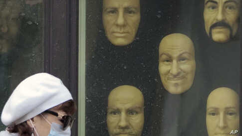 A woman wearing a face mask walks past wax faces displayed in a window of a wax museum in St.Petersburg, Russia, May 4, 2020.