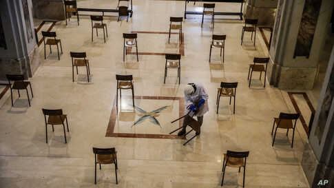 A woman cleans SS. Quirico and Giulitta Church in Giussano, northern Italy, Friday, May 15, 2020, also placing chairs at the…