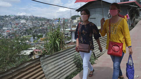 Naga girls wearing face masks walk on a street in Kohima, capital of the northeastern Indian state of Nagaland, Friday, May 29,…