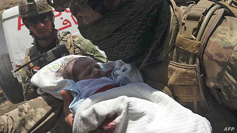 An Afghan security personnel carries a newborn baby from a hospital, at the site of an attack in Kabul. Gunmen stormed the government-run hospital in Dasht-e-Barchi area, killing at least 13 people and injuring 15 others.