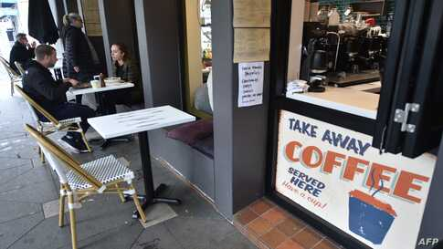 FILE - Customers eat in a cafe after more than seven weeks of coronavirus restrictions, in Sydney, Australia, May 15, 2020.