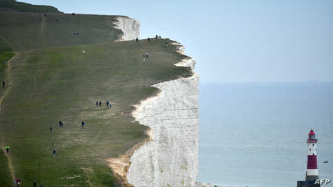 People walk along the cliff-top above the lighthouse at Beachy Head near Eastbourne on the south coast of England following an easing of lockdown rules in England during the COVID-19 pandemic.