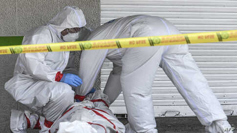 Police officers wearing protective suits remove the corpse of a man who died in the street in Medellin, Colombia, May 6, 2020, amid the Covid-19 coronavirus pandemic.