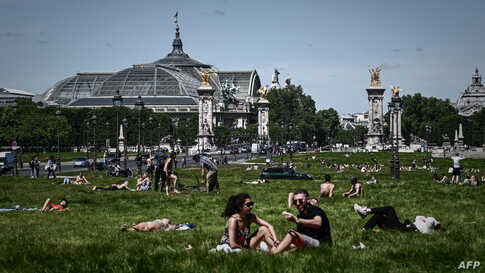 People enjoy a sunny day on a lawn near the Grand Palais and the Pont Alexandre III bridge in Paris as France partially lifted restrictions to prevent the spread of the COVID-19.