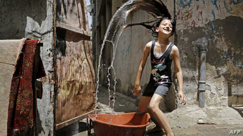 A Palestinian girl plays with water to cool off during a heatwave at Bureij refugee camp in the central Gaza Strip.