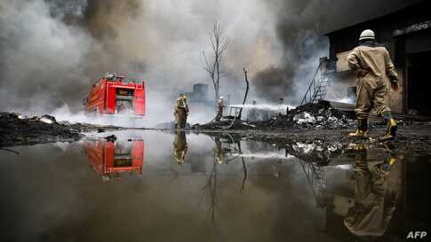 A firefighter extinguishes a fire broke out at a warehouse in New Delhi, India.