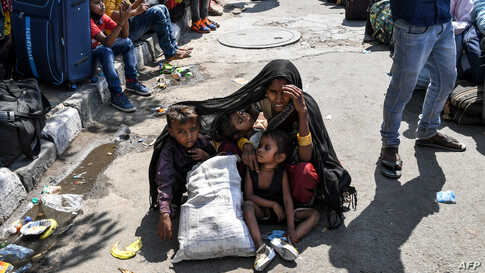 A woman covers her children with a shawl to protect them from the sun as she waits with other migrant workers and families for a train going to their home towns after the government eased a nationwide coronavirus lockdown in New Delhi, India.