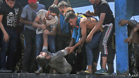 Protesters carry an injured man during clashes with security forces on Al-Jumhuriyah bridge in the capital Baghdad, Iraq, following an anti-government demonstration.